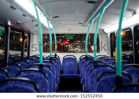Rows of empty blue seats on a London Double Decker Bus at night - stock photo