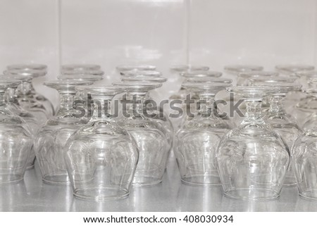 Rows of empty cognac glasses on the showcase. Restaurant utensils. Shallow focus