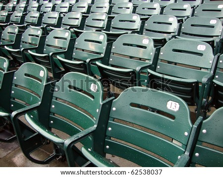 Rows of empty wet green stadium seats, seats number 13, 12, 11. AT&T Park San Francisco - stock photo