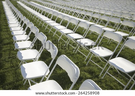 Rows of empty white chairs in grassy field in Washington, DC