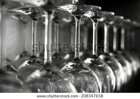 Rows of empty wine glasses on the showcase, black and white photography - stock photo