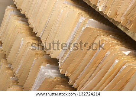 Rows of File Folders Arranged on Shelf with Client Data in Office Setting - stock photo