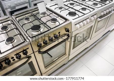 rows of gas stoves selling in home appliance store - stock photo