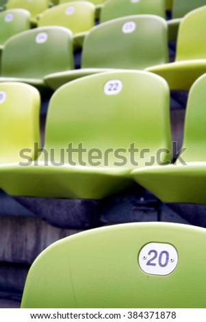 Rows of green chairs in a stadium - stock photo