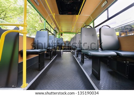 Rows of grey seats inside clear saloon of empty city bus with skylight.