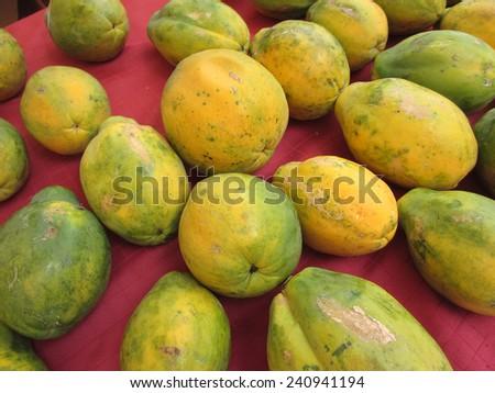Rows of Hawaiian big rip papayas on red cloth at a farmer's market in Hawaii. - stock photo