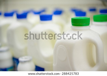 Rows of large milk bottles in fridge in supermarket