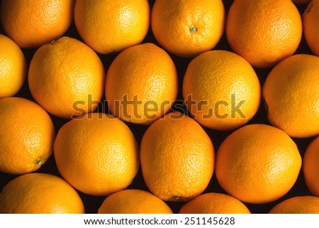 Rows of many ripe fresh oranges as background over black Closeup Photo - stock photo