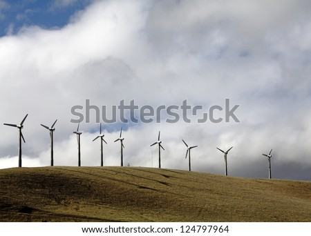 Rows of modern windmill in an energy wind farm on top of a hill against a dramatic cloudy sky. - stock photo