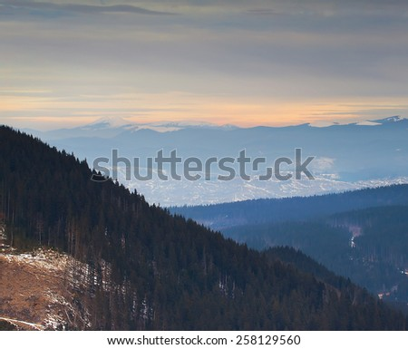 Rows of mountains in the morning mist under beautiful clouds - stock photo