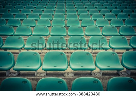 Rows of multilevel empty green plastic grandstand seats with number at an outdoor sport stadium in Singapore. Seamless pattern of outdoor stadium/arena chairs on main stand. Sport background concept.