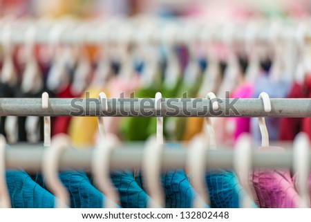 Rows of new colorful clothing on hangers at shop in foreground and background. Great choice of casual clothes of different colors. Apparel ready for sale. Going shopping. Trade and commerce. - stock photo