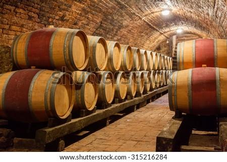 Rows of oak barrels in underground wine cellar - stock photo