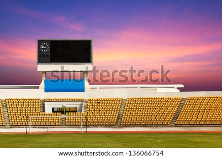 Rows of orange seats on the stadium with scoreboard displaying clock above them - stock photo