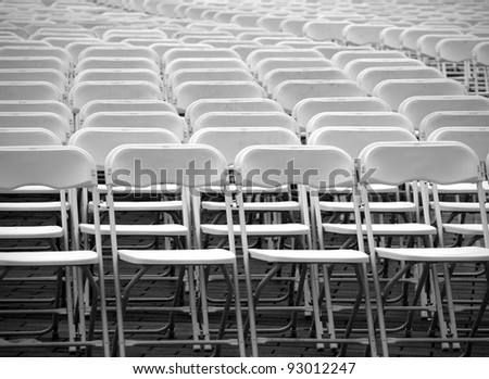 Rows of plastic chairs are lined up for an outdoor concert - stock photo