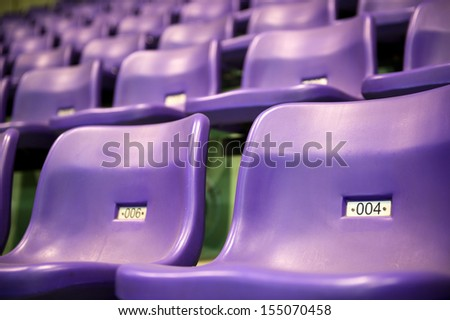 Rows of purple stadium seats with numbers. - stock photo
