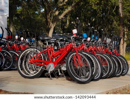 Rows of red bicycles lined up and ready to be rented on a sunny day at a vacation destination. - stock photo