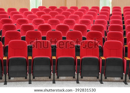rows of red chairs in auditorium - stock photo