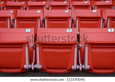 Rows of red football stadium seats with numbers - stock photo