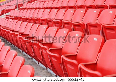 Rows of red football stadium seats with numbers. - stock photo