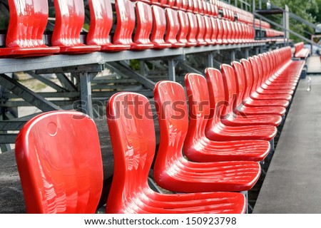 Rows of red mini-football stadium empty seats - stock photo