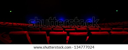 Rows of red seats in a dark theatre with blue lights shining on the screen. - stock photo