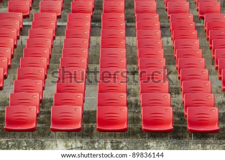 Rows of red spectator seating in a sports stadium - stock photo