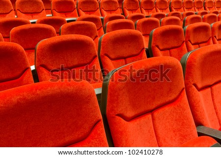 Rows of red velvet theater seating. - stock photo
