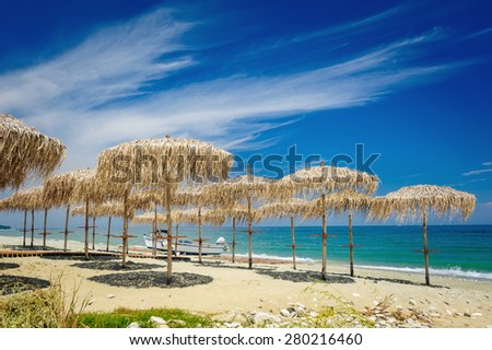 Rows of reed umbrellas on the sea beach  - stock photo