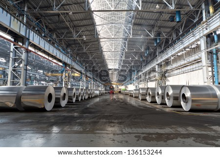 Rows of rolls of aluminum lie in production shop of plant. - stock photo