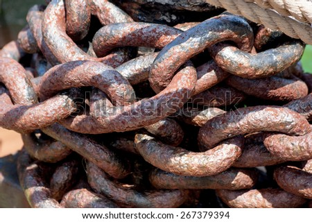 Rows of rusted chains. Heavy rusted metal chain. Big links of the chain covered with red rust with shadows and hotspots - stock photo
