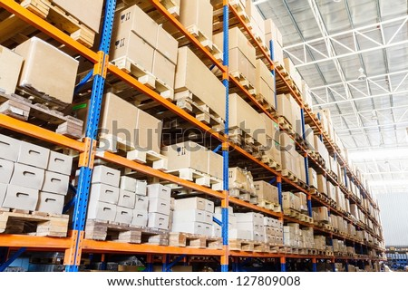 Rows of shelves with boxes in factory warehouse - stock photo
