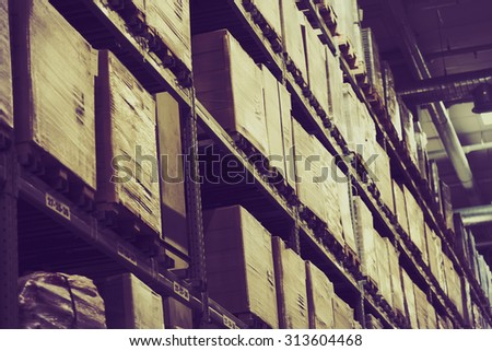 Rows of shelves with boxes in factory warehouse, vintage filter. - stock photo