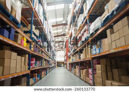 Rows of shelves with boxes in warehouse - stock photo