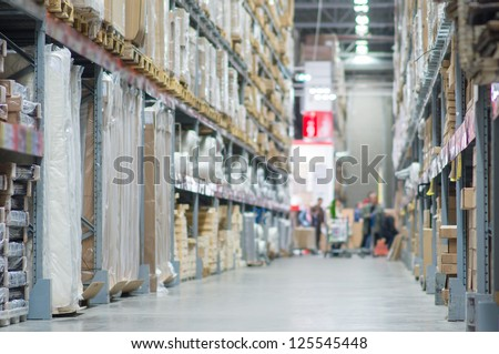 Rows of shelves with huge cardboard boxes in modern warehouse