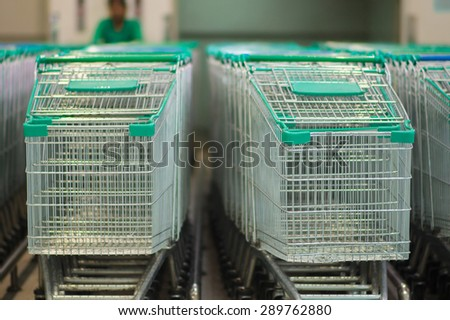 Rows of shopping carts in front of supermarket entrance - stock photo