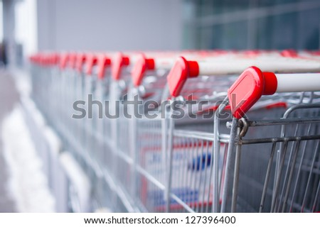 Rows of shopping carts on car park near entrance of supermarket - stock photo
