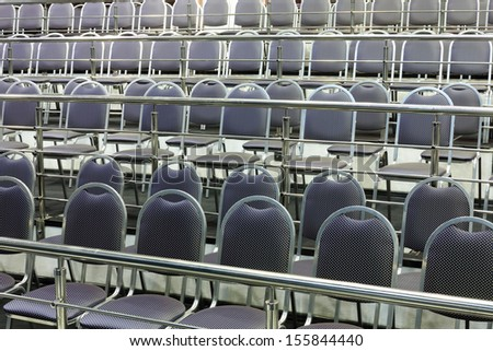 Rows of simple chairs with handrails in modern hall for business meetings.   - stock photo