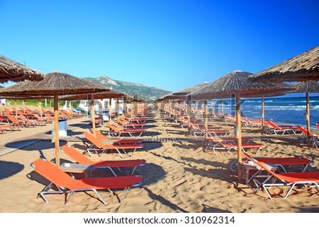 Rows of straw umbrellas and loungers at banana beach, Zakynthos, Greece. - stock photo
