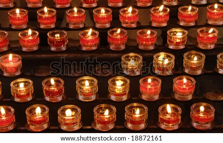Rows of the burning candles in a church