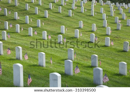 Rows of tombstones with American flags at Arlington National Cemetery on Memorial Day - stock photo