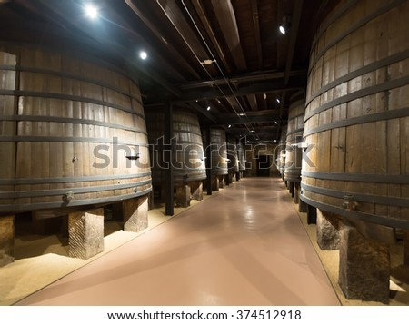 Rows of vertical wooden barrels in old cellar - stock photo