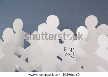 Rows of white paper people chains and one individual has the words Help Me written on it. Concept image for stress,mental health, coping with modern life or looking for help to escape the herd.