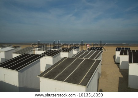 Rows of white wooden beach huts, with black rooftops, facing the sea on a sandy beach with a blue cloudy sky, Ostende, Belgium