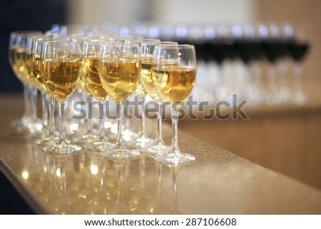 Rows of wine glasses on bar counter - stock photo