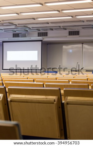 Rows of wood chairs in auditorium and board hanging on wall