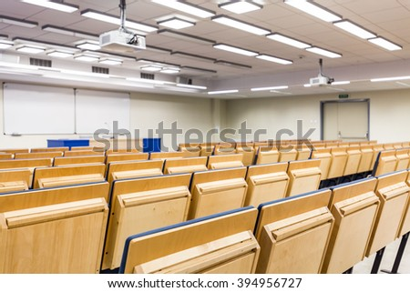 Rows of wood chairs in light auditorium
