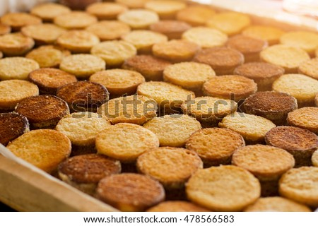 Rows of yellow cookies. Biscuits under sunlight. Mass production of pastry. Nation's favorite dessert.
