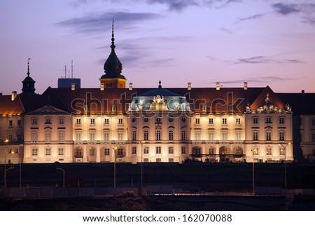 Royal Castle (Polish: Zamek Krolewski) illuminated at dusk in the Old Town of Warsaw, Poland. - stock photo