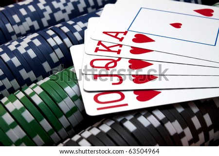 Royal Flush A heart royal flush sitting on rows of gaming chips. Horizontal. - stock photo
